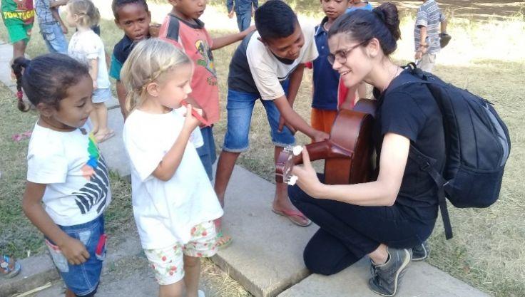 Voluntária se ajoelha para tocar guitarra com crianças